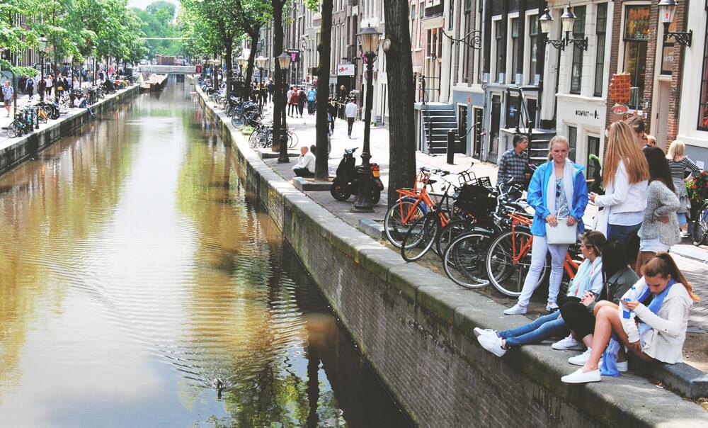 oameni-din-amsterdam-pe malul canalului